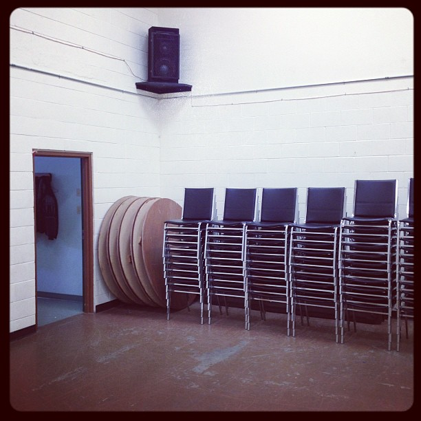 Searchmont Community Hall with tables and chairs.  Speakers are mounted in the room for events.